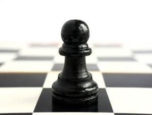 Sjakkbrikke (bonde) i nærbilde - på vei til å bevege seg mot en usikker framtid